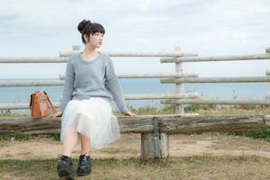 海沿いのベンチに座る女性ri